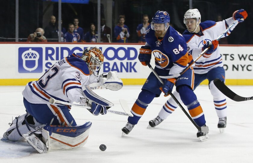 Edmonton Oilers goalie Cam Talbot (33) makes a save with Oilers defenseman Mark Fayne (5) defending against New York Islanders center Mikhail Grabovski (84), of Germany, in the second period of an NHL hockey game in New York, Sunday, Feb. 7, 2016. (AP Photo/Kathy Willens)