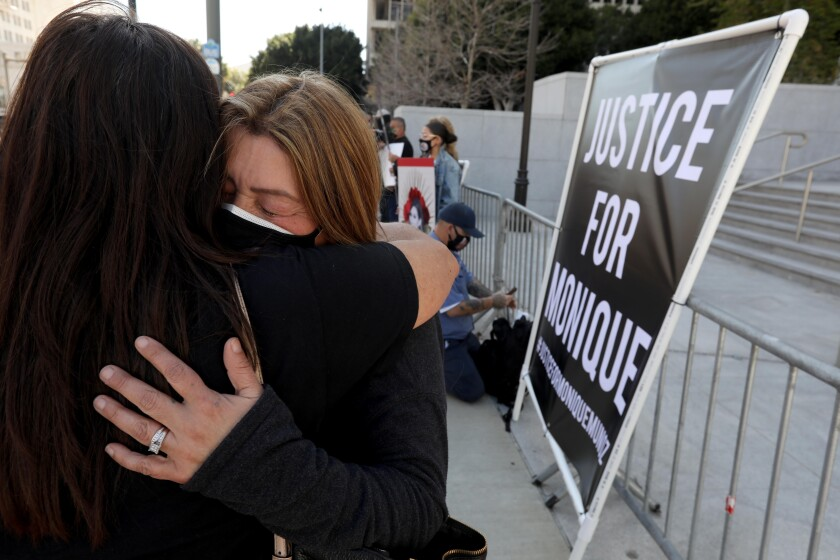"""Two women hug near a sign that reads """"Justice for Monique."""""""