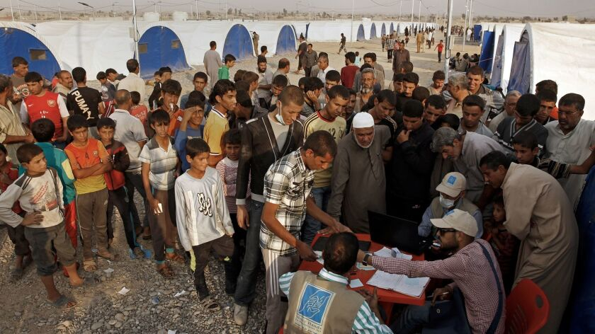 Residents who fled the fighting in Mosul line up for aid from the World Food Program.