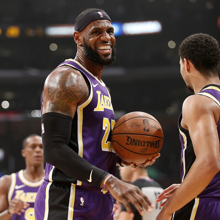 Lakers forward LeBron James celebrates a basket against the Timberwolves by teammate Josh Hart.