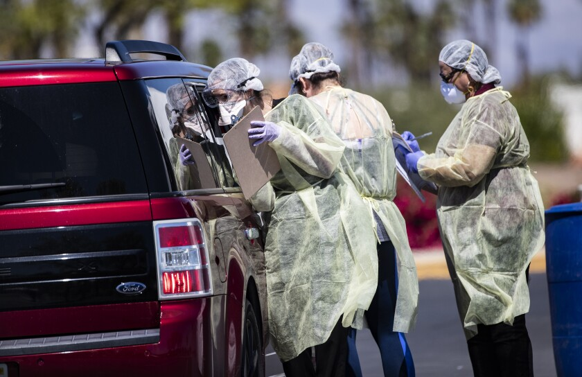 Riverside County medical personnel screen a car of four people at a coronavirus drive-though testing facility in Indian Wells.
