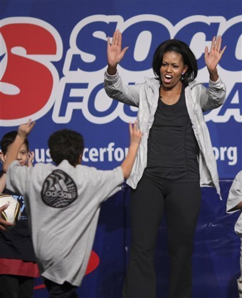 First Lady Michelle Obama joins kids at a free soccer clinic as part of her campaign to improve fitness and combat obesity in children, Friday, March 5, 2010, in Washington. (AP Photo/J. Scott Applewhite)