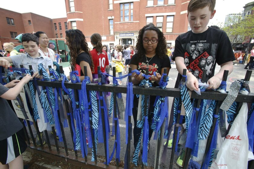 In this Friday, May 15, 2015 photo, students tie cloth strips on a fence outside the Nettelhorst School in Chicago. With the help of the students and other volunteers, Boy Scout David Fite decorated the street scene in preparation for the city's nearby Gay Pride Parade. The school is in the heart o