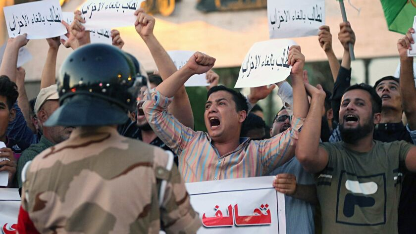 Iraqi protesters chant slogans demanding services and jobs during a demonstration in Tahrir Square,