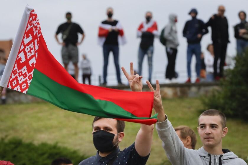 Varias personas con la bandera de Bielorrusia protestan en la calle