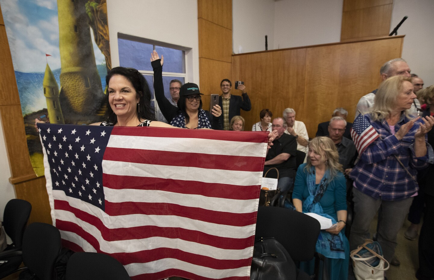 Lisa Collins holds an American flag during a Laguna Beach City Council meeting Tuesday in which the council considered the flag design on city police cars.