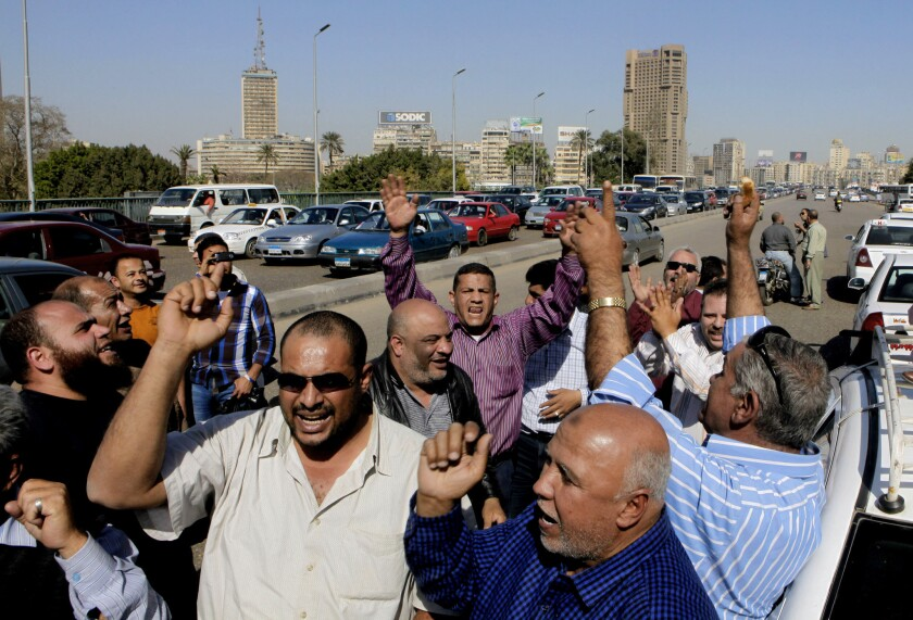 Egyptian taxi drivers shout slogans against President Mohammed Morsi as they block part of the 6th of October bridge in central Cairo.