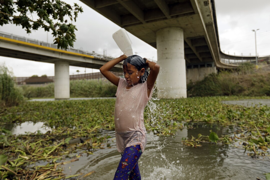 A migrant girl washes her hair.