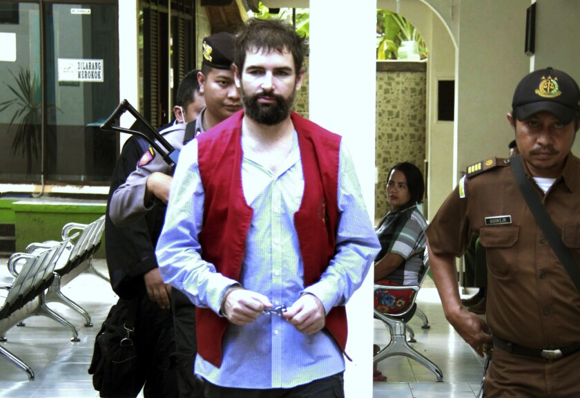 FILE - In this Monday, May 20, 2019 file photo, officers escort French national Felix Dorfin, center, upon arrival for his sentencing hearing at a district court in Mataram, Lombok Island, Indonesia. Authorities put the Frenchman in a solitary confinement after trying to escape from jail in Indonesia's tourist island of Lombok for a second time, prison official said Friday, Oct. 4. (AP Photo)