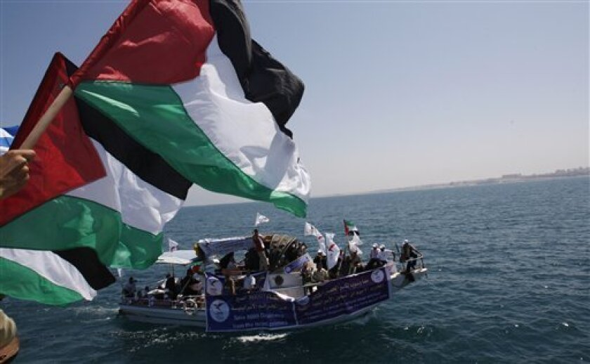 Palestinian flags wave in Gaza port, foreground, and Palestinians ride a boat in Gaza waters, a day before a flotilla of aid ships is expected to try and sail into the blockaded territory, in Gaza city, Sunday, May 30, 2010. Hundreds of pro-Palestinian activists on seven ships prepared to set sail