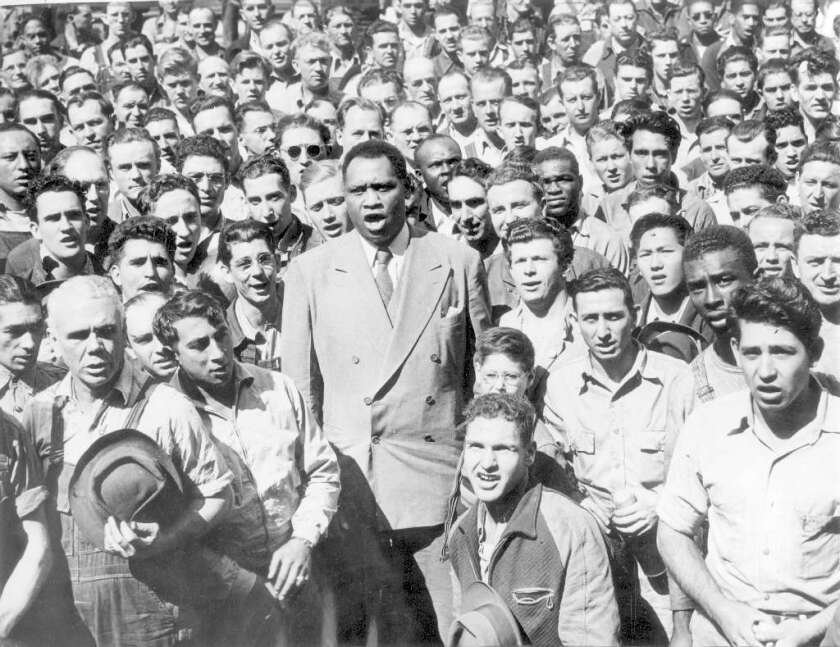 """Paul Robeson, center, leads workers at an Oakland shipyard in a rendition of """"The Star Spangled Banner"""" in 1942. Robeson is the subject of two different plays that will run at nearly the same time in Los Angeles next spring."""