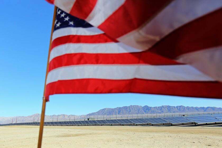 An American flag flutters in the wind at the 550-megawatt Desert Sunlight solar farm in Desert Center, Calif.