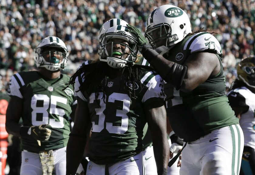New York Jets running back Chris Ivory (33) celebrates with guard James Carpenter (77) after scoring a touchdown against the Jacksonville Jaguars during the first quarter of an NFL football game, Sunday, Nov. 8, 2015, in East Rutherford, N.J. (AP Photo/Seth Wenig)