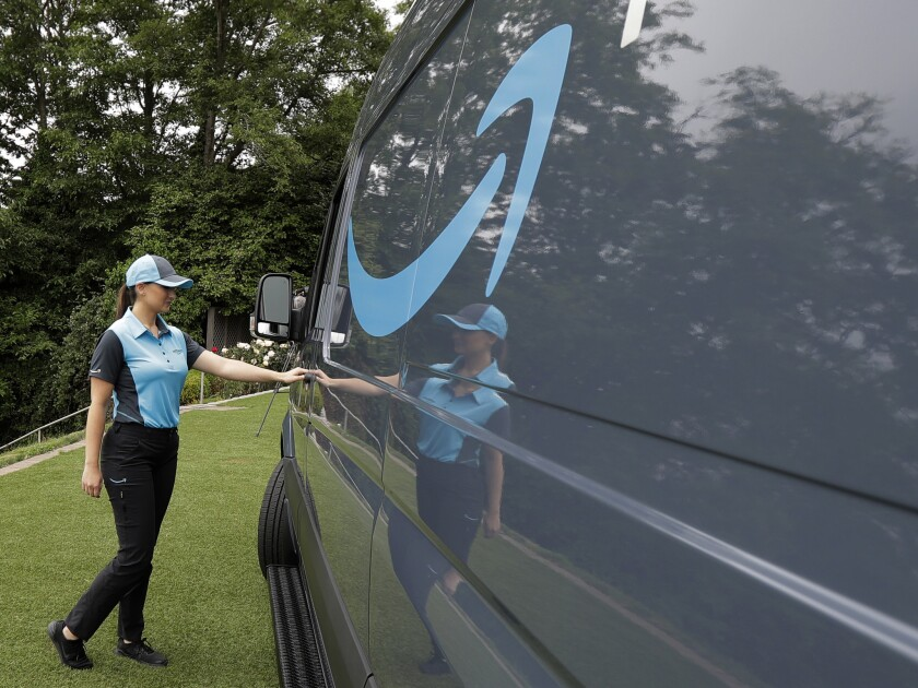 Parisa Sadrzadeh, a senior manager of logistics for Amazon.com, opens the door of an Amazon-branded delivery van at the request of a photographer, Wednesday, June 27, 2018, following a media event in Seattle to announce a new program for entrepreneurs to sign on to use Amazon Prime-branded vans and get support from the company as they form businesses to deliver Amazon packages.