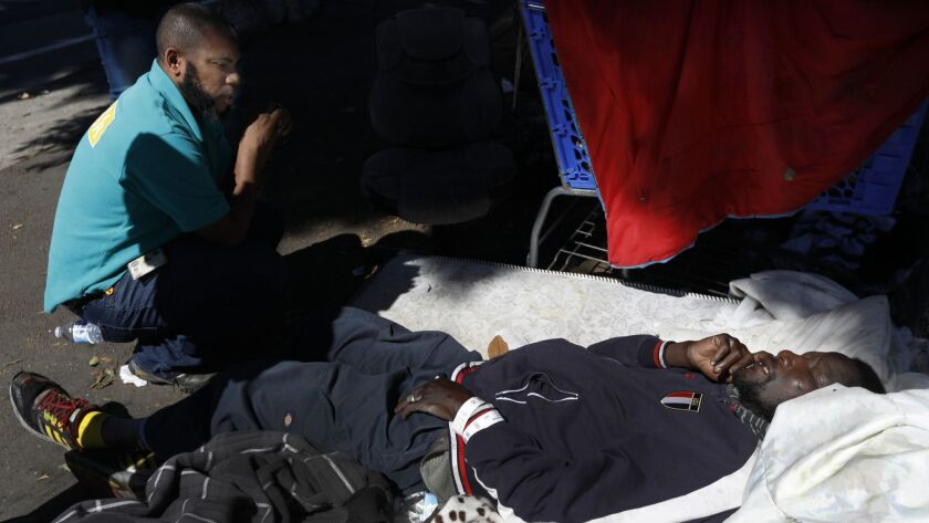 Outreach worker Geoffrey Goosby offers help to a man lying on a sidewalk mattress in south Los Angeles. The man declined help and refused to be taken to a hospital.