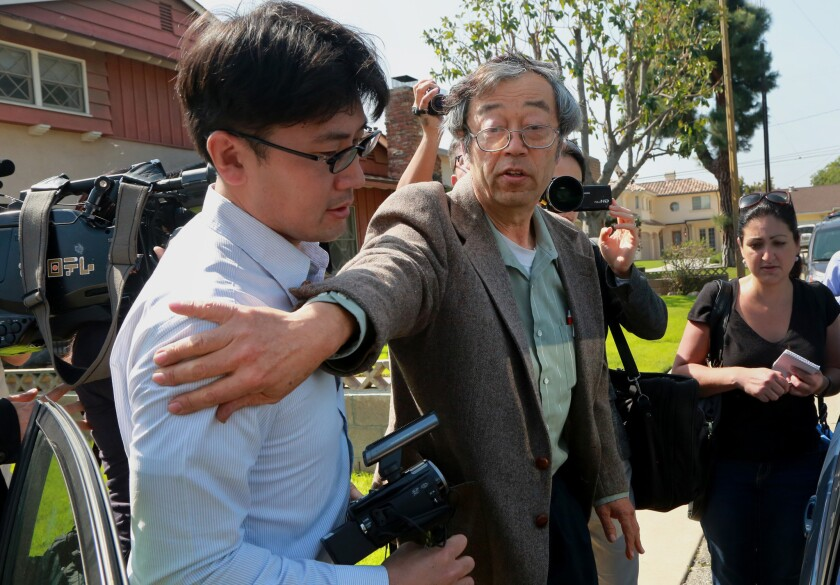 Dorian Satoshi Nakamoto, identified by Newsweek magazine as the founder of bitcoin, center, exits his home surrounded by members of the media in Temple City.
