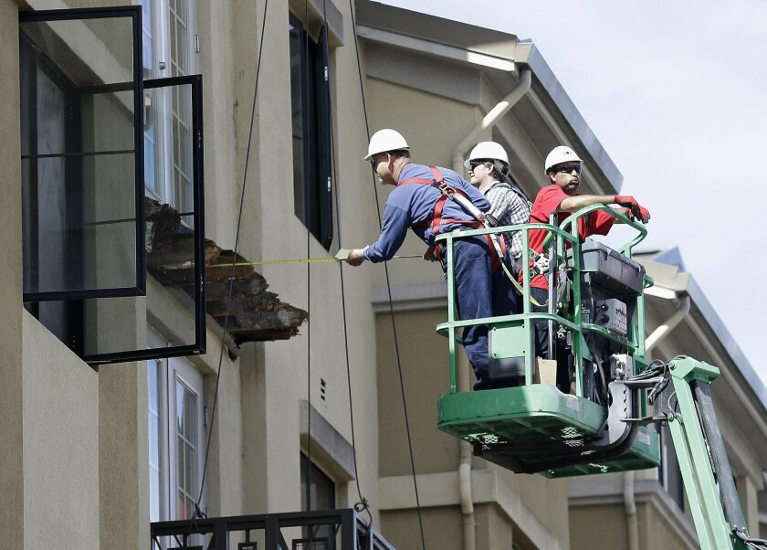 FILE- In this Wednesday, June 17, 2015 file photo, a worker measures near the remaining wood from an apartment building balcony that collapsed in Berkeley, Calif. The balcony broke loose from the building during a 21st birthday party early Tuesday, June 16, 2015, killing several people and seriousl