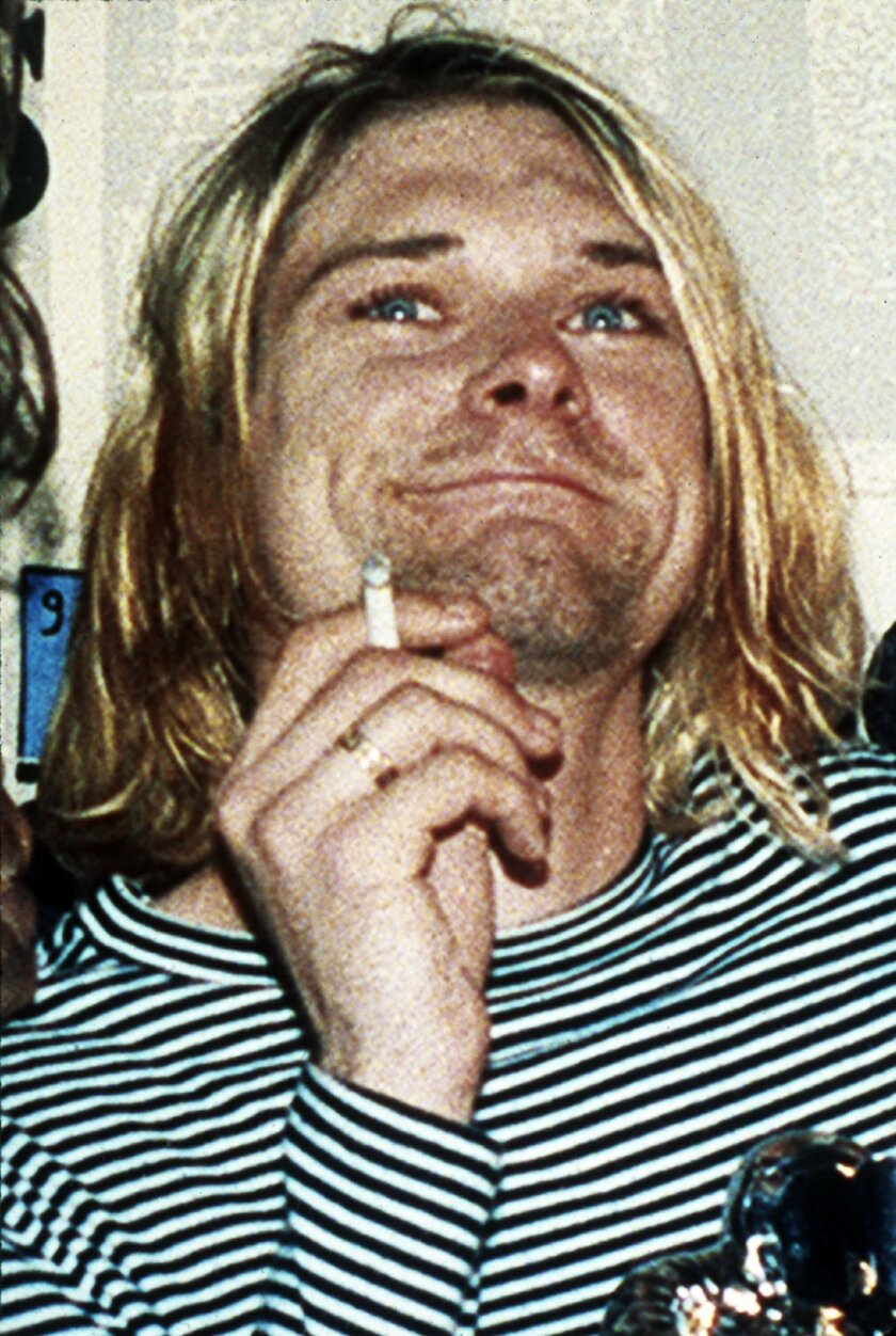 "FILE - This 1993 file photo shows Kurt Cobain, lead singer of Nirvana. A handwritten note police discovered in Kurt Cobain's wallet after his suicide disparages his wife Courtney Love. CBS News reports Wednesday, April 30, 2014, that the note was taken from Cobain's wallet when police arrived at his home on April 8, 1994, after Cobain fatally shot himself. The note was never made public. CBS obtained it from the Seattle Police via a public information request. The network reports that the undated note, apparently written by Cobain on stationery from San Francisco's Phoenix Hotel, is written like a mock wedding vow. It references Love as Cobain's ""lawful shredded wife"" who would be ""siphoning"" his money for drugs. (AP Photo/Mark J.Terrill, File)"