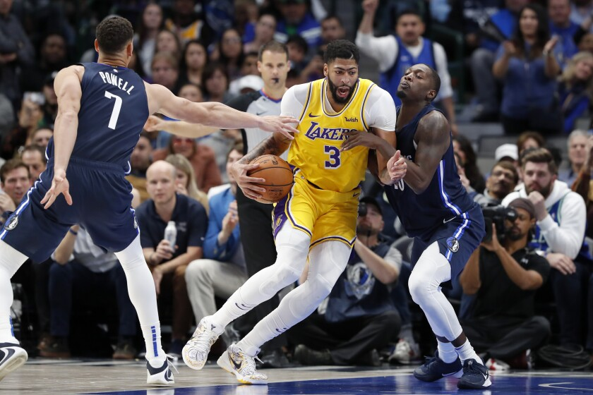 The Lakers' Anthony Davis, who scored 31 points, drives against the Mavericks' Dwight Powell and Dorian Finney-Smith.