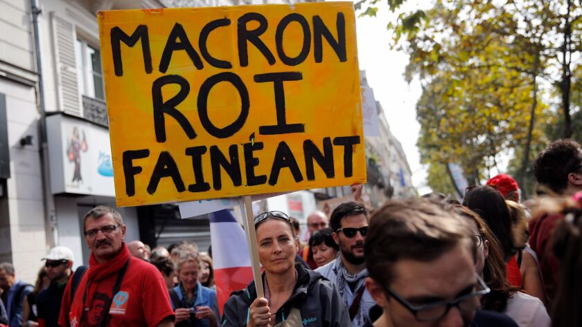 A demonstrator holds a placard referring to Emmanuel Macron as the slacker king during a protest in