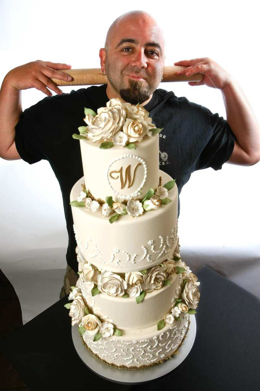 "Duff Goldman, the cake baker behind the ""Ace of Cakes"" TV show, is photographed next to one of his designer cakes, a floral wedding cake at Charm City Cakes West, his new bakery in Los Angeles."