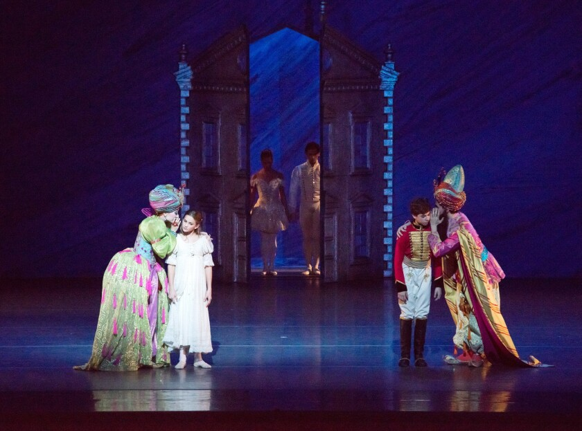 Sugar Plum Fairy (Zhong-Jing Fang), far left, and Majordomo (Patrick Frenette), far right, share secrets with young Clara (Ava McLarand) and Nutcracker Boy (Joshua Binowitz), with the grown-up Clara/Princess (Misty Copeland) and the Nutcracker/Prince (Herman Cornejo) upstage.
