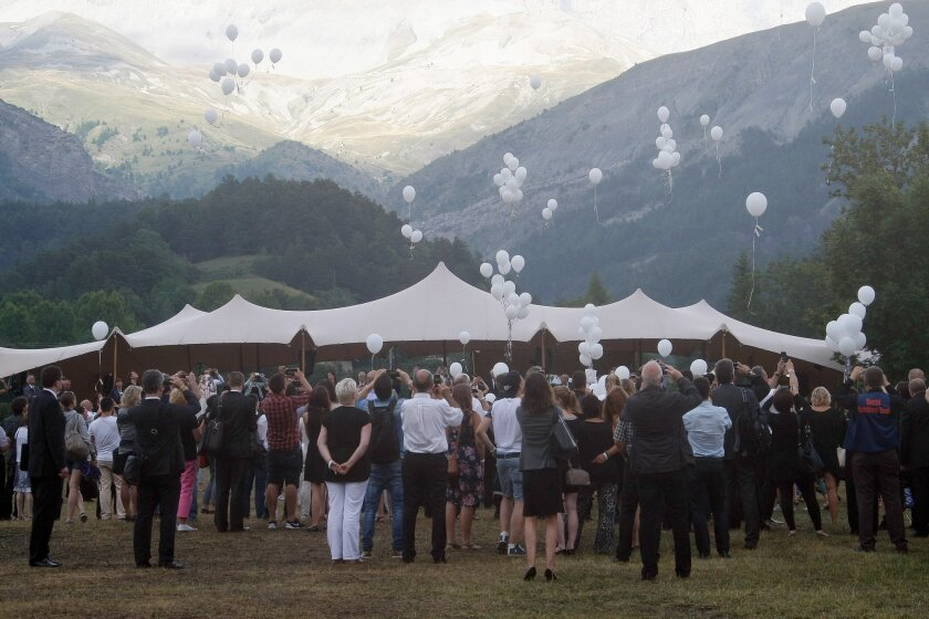 Families of Germanwings victims release white balloons after an homage ceremony in front of a stele, in Le Vernet, French Alps, Friday, July 24, 2015. Families of those killed in the Germanwings crash are in the Alpine village where the plane went down to commemorate the dead and bury unidentified remains. Friday's ceremony in Le Vernet takes place exactly four months after the co-pilot is believed to have intentionally crashed the Airbus 320 into a nearby mountain, killing all 150 people on board. The town sub-prefect, Patricia Willaert, estimates 300 family members are attending. Most of the dead were German and Spanish. (AP Photo/Claude Paris)