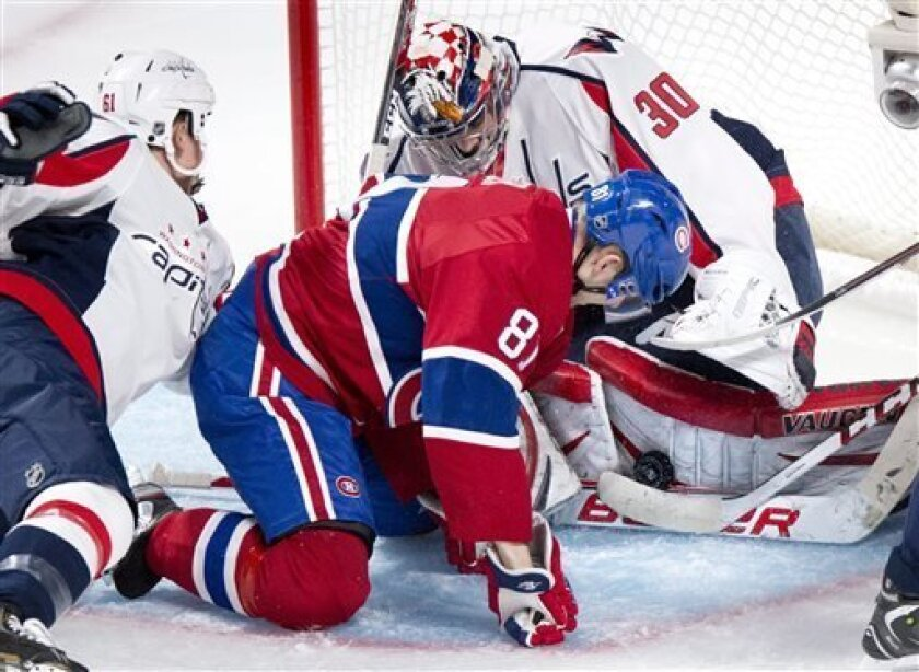 Washington Capitals goalie Michal Neuvirth stops the puck in front of Montreal Canadiens' Lars Eller during second period NHL hockey action Tuesday, April 9, 2013 in Montreal. (AP Photo/The Canadian Press, Paul Chiasson)