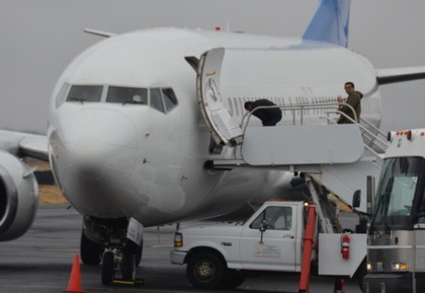 An unidentified detainee, right, in handcuffs locked to a belt chain, manages to wave to activists as he boards a U.S. Immigration and Customs Enforcement flight in Yakima, Wash.