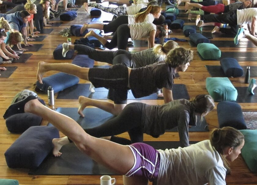 In this May 26, 2016 photo, former world-class snowboarder Kevin Pearce, third from bottom, participates in a yoga class at a retreat in Lincoln, Vt., hosted by the Love Your Brain Foundation, started by Pearce and his brother. A near-fatal halfpipe crash while training for the 2010 Olympics ended