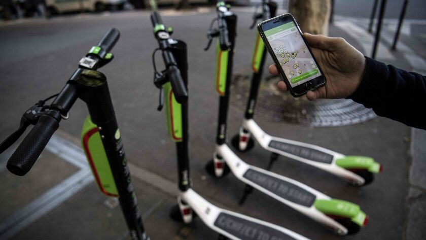 A man looks at the app that enables him to check on the availability of Lime's electric scooters.