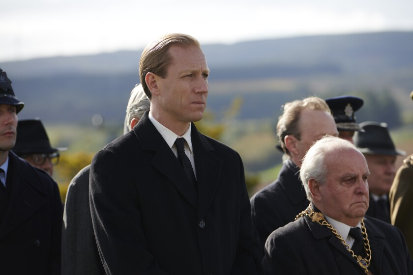 Tobias Menzies as Prince Philip, standing in a small crowd