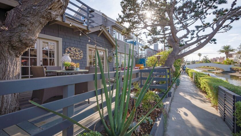 A blue clapboard house with a patio, and matching blue fence sits across the canal in Venice, California