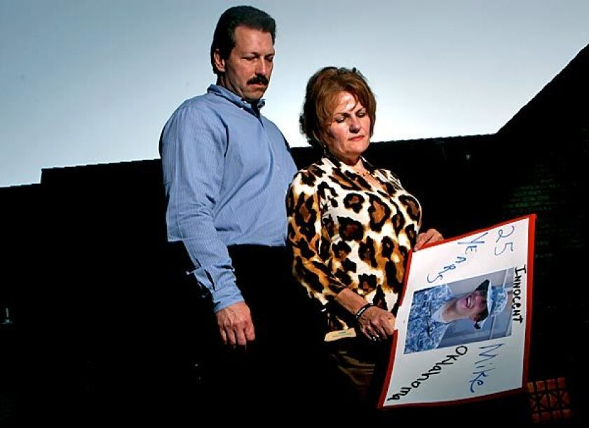 Scott and Vicki Behenna with a sign in Edmond, Okla., picturing their son 1st Lt. Michael Behenna.