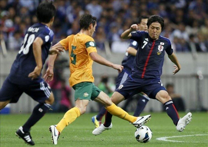 El delantero japonés Shinji Okazaki (der), disputa el balón con el australiano Matthew McKay (izq) durante el encuentro de clasificación para el Mundial de Brasil 2014 entre ambos países celebrado en el estadio Saitama, al norte de Tokio, en Japón, hoy. EFE