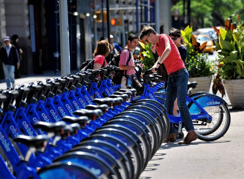 A couple pick out bicycles to rent from the CitiBike bike sharing program in New York. Citibank is a sponsor of the program, which launched last month.