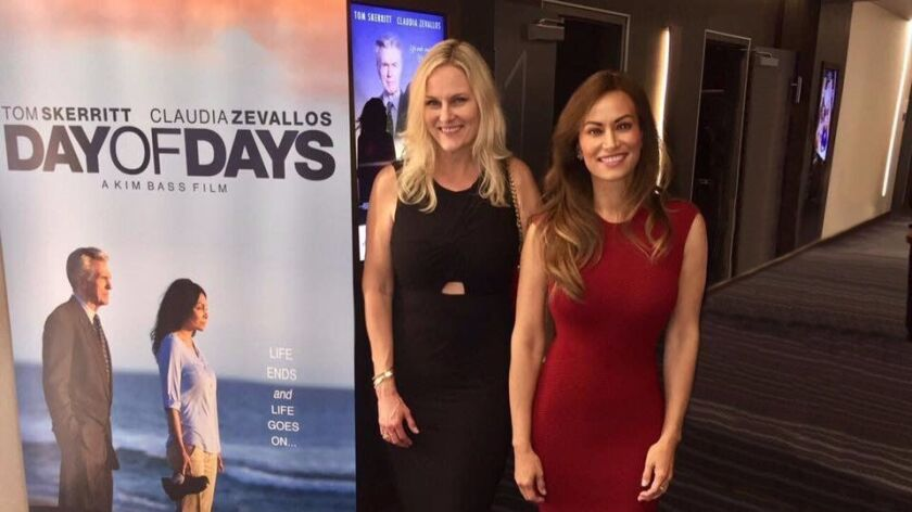 """Annette Caton, left, with Lena Evans standing by a poster promoting a movie, """"Dad of Days,"""" starring"""