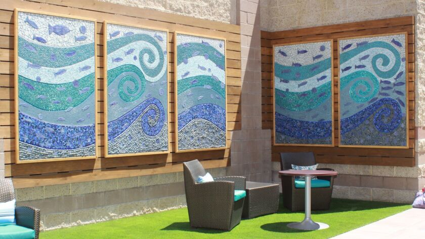 The outdoor donor wall recognizes major benefactors with small fish on an-ocean inspired mural desig