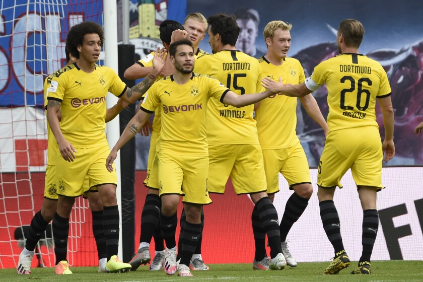Dortmund's Erling Braut Haaland, center background, celebrates with his teammates after he scored his side's first goal during the German Bundesliga soccer match between RB Leipzig and Borussia Dortmund in Leipzig, Germany, Saturday, June 20, 2020. (AP Photo/Jens Meyer, Pool)