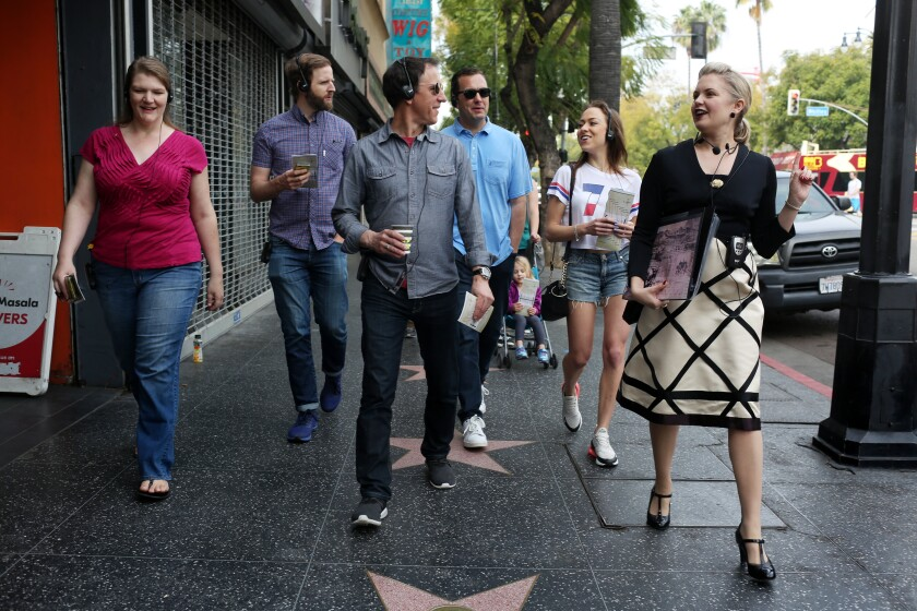 A group takes a walking tour along the Hollywood Walk of Fame.