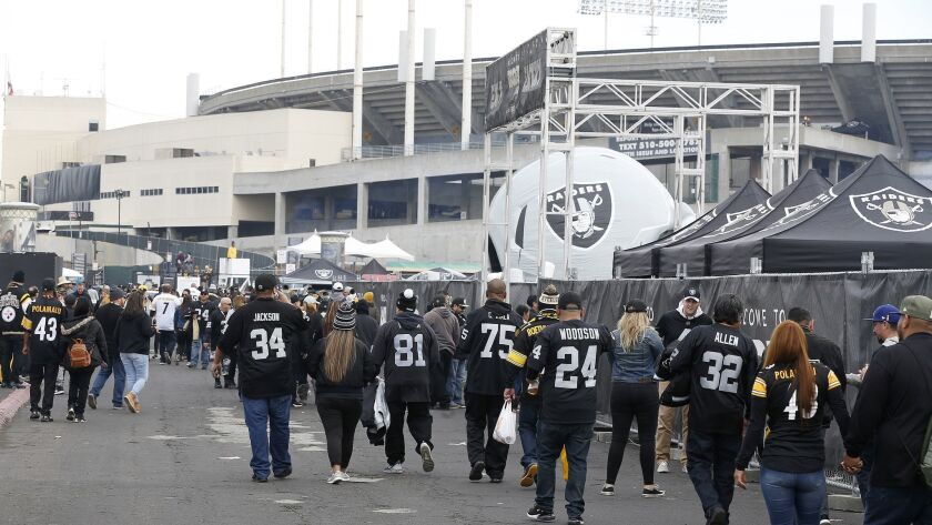 Fans tailgate outside of Oakland Alameda County Coliseum before a game between the Oakland Raiders and the Pittsburgh Steelers.