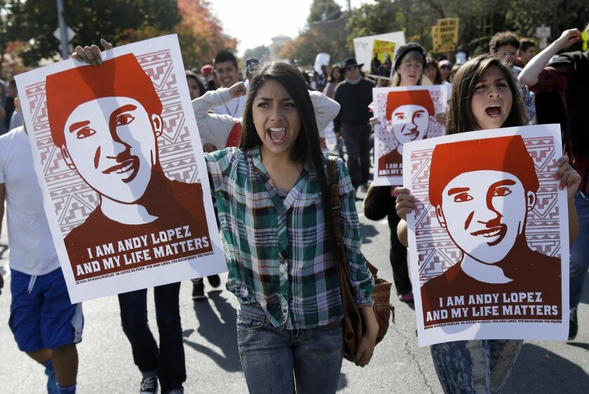 FILE -- In this Oct. 29, 2013, file photo, protesters hold an image of shooting victim Andy Lopez, during a march in Santa Rosa, Calif.  Lopez was shot and killed by a Sonoma County deputy after authorities say the deputy mistook an airsoft type gun Lopez was carrying for an assault rifle.  A measu