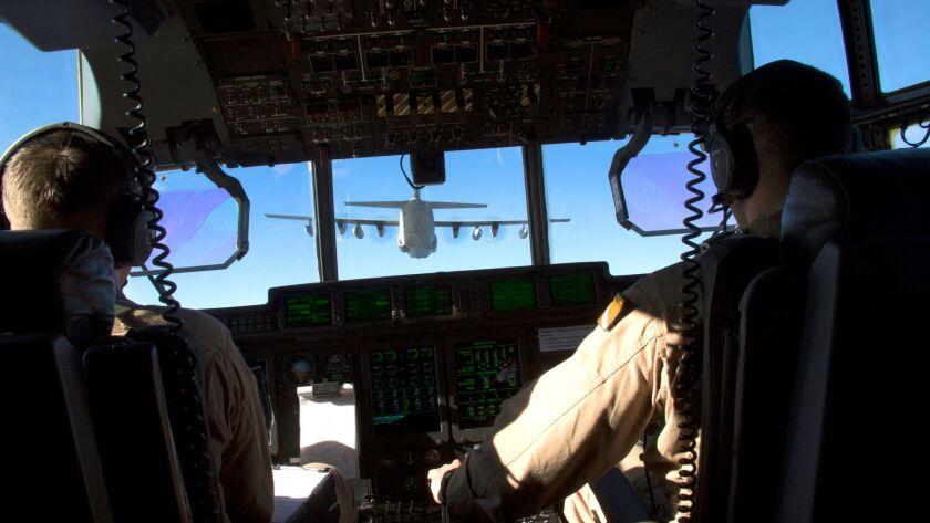 Marine captains and KC-130J pilots Sean Elliott (left) and Orlando Samudio conduct a formation fligh