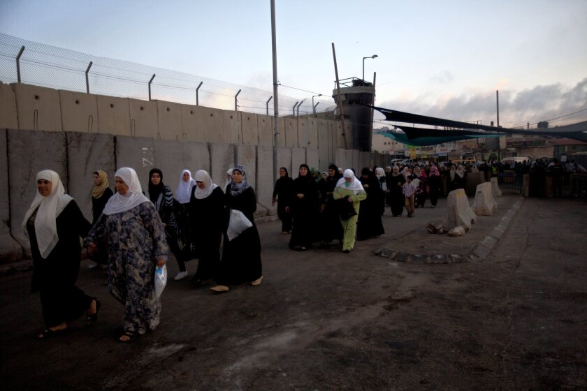 Palestinian women cross the Qalandia checkpoint, between the West Bank city of Ramallah and Jerusalem, on their way to pray at the Al Aqsa Mosque during the Muslim holy month of Ramadan.