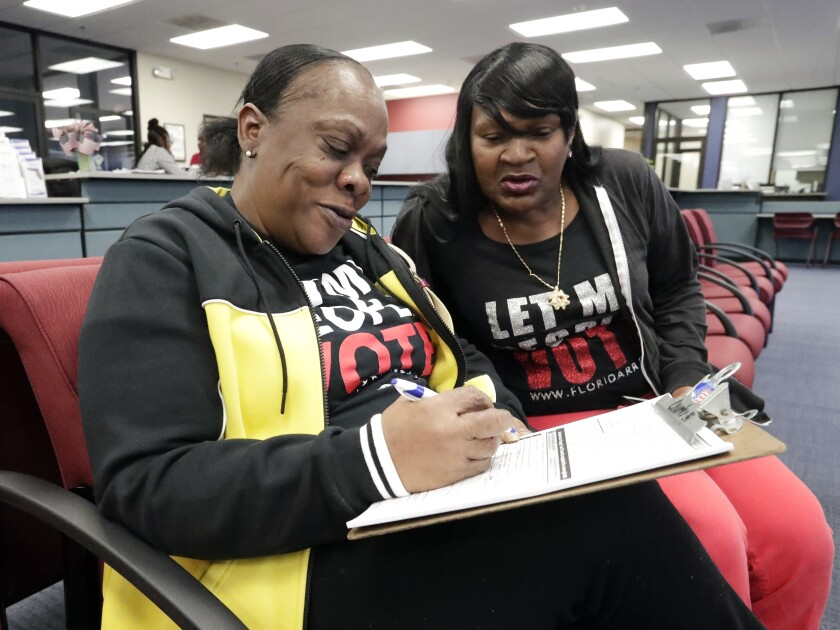 Gale Buswell watches her friend, former felon Yolanda Wilcox, fill out a voter registration form in Orlando, Fla., on Jan. 8.