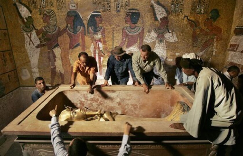 FILE - In this Sunday, Nov. 4, 2007 file photo, Egypt's antiquities chief Dr. Zahi Hawass, center, supervises the removal of King Tut from his stone sarcophagus in his underground tomb in the famed Valley of the Kings in Luxor, Egypt. Egypt will soon reveal the results of DNA tests made on the world's most famous ancient king, the young Pharaoh Tutankhamun, to answer lingering mysteries over his lineage, said the antiquities department Sunday, Jan. 31, 2010. (AP Photo/Ben Curtis, Pool, File)
