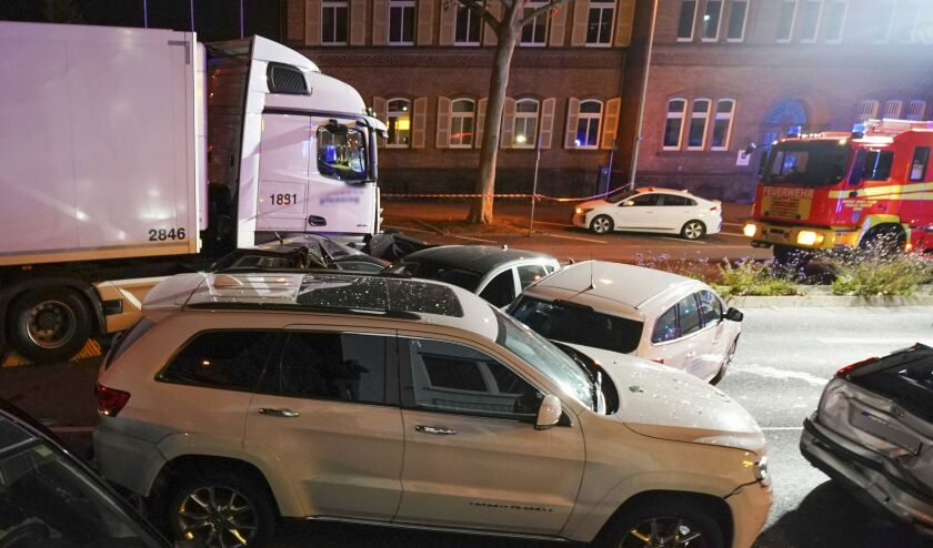 In this Monday, Oct. 7, 2019 photo s truck stands between damaged cars in Limburg, Germany. The truck drove into a line of eight cars in Limburg late Monday afternoon, pushing the vehicles into each other. Police said seven people were taken to hospitals and the driver also was slightly injured. He was detained. (Thorsten Wagner/dpa via AP)