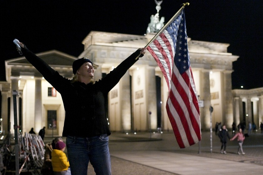 Marianne Hoenow from Connecticut in the US celebrates the victory of President-elect Joe Biden and Vice President-elect Kamala Harris in front of the Brandenbug Gate next to the United States embassy in Berlin, Germany, Saturday, Nov. 7, 2020. Biden defeated President Donald Trump to become the 46th president of the United States on Saturday, positioning himself to lead a nation gripped by the historic pandemic and a confluence of economic and social turmoil. (Photo/Markus Schreiber)