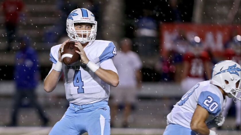 Corona Del Mar football QB #4 Ethan Garbers throws the ball with rain coming down in away game vs. L