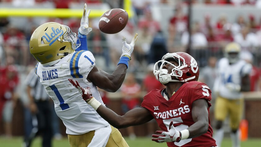 UCLA cornerback Darnay Holmes intercepts a pass intended for Sooners receiver Marquise Brown during a game Sept. 14 at the Rose Bowl.